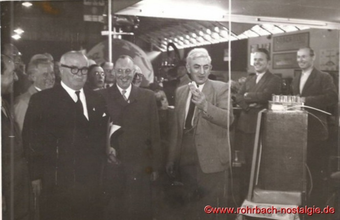 """1950 Saarmesse in Saarbrücken: Der saarl. Ministerpräsident Johannes Hoffmann (links im Bild) besucht den Stand der Radiofirma """" JOBA """". Firmenbesitzer Josef Bayer (Bildmitte mit grauen Haaren)"""