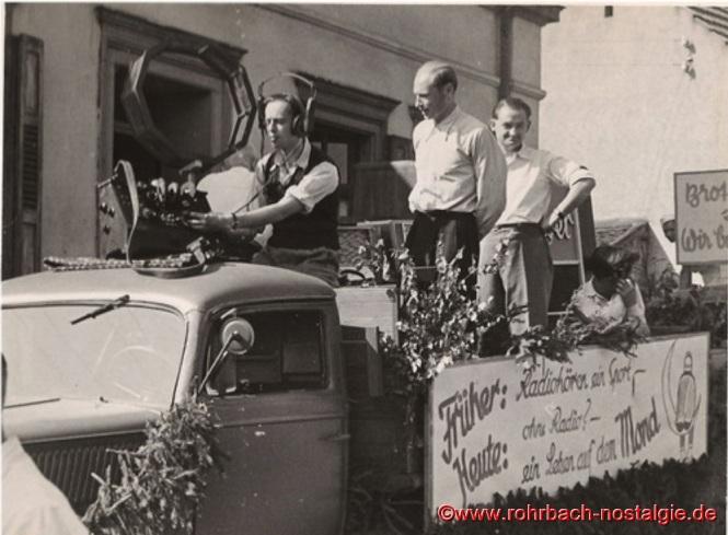 """Bei dem Festumzug """"100 Jahre selbständige Gemeinde Rohrbach"""" am 4. September 1949 fährt dieser Wagen mit und macht Reklame für JOBA-Radios. Der Chef der Firma, Josef Bayer, sitzt im ersten Foto auf der Ladefläche (mit Sonnenbrille und weißem Hemd). Die Aufschriften auf dem Wagen lauten: Erstes Bild: """"Radio hören... heißt doppelt leben."""" -- """"Mit Lip ist es genau ... 15 Uhr!"""" (Lip ist eine französische Uhrenmarke, für die mit diesen Worten eine Zeitlang bei der Zeitansage Werbung gemacht wird.) -- """"Versuch dein Glück"""" / """"Der runde Tisch"""" / """"Die Saarlandbrille"""" (Namen von drei beliebten Sendungen von Radio Saarbrücken.) Unteres Bild: """"Früher: Radiohören ein Sport - Heute: ohne Radio? - ein Leben auf dem Mond."""" (Man darf nicht vergessen, dass der Beginn regelmäßiger Rundfunksendungen in Deutschland damals gerade erst etwa 25 Jahre zurückliegt!)"""