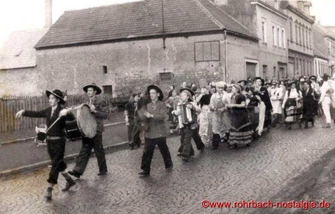 Um 1952 Die Sonny Boys führen den Fastnachtsumzug in Rohrbach an. Im Hintergrund Metzgerei Rubeck und Bäckerei Haberer