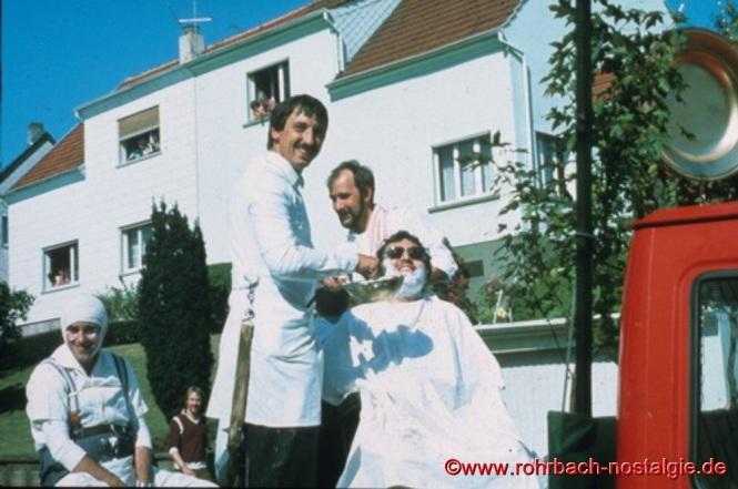 """Dorfbarbier (""""Balweerer"""") (gestaltet vom Tischtennisclub Rohrbach). Dorfbarbier Peter Rohe rasiert Guido Kapp. Die """"Balweerer"""" arbeiteten mittwochs und samstags nach ihrer Schicht auf der Grube. Sie trugen einen Holzkasten mit ihrem Handwerkszeug unterm Arm. Die Berühmtesten damals waren """"Wolle Michel"""", """"es Kitzje"""", """"Fetzes Hannes"""", """"Fetzes Joseb"""" und """"Fetzes Fritz""""."""