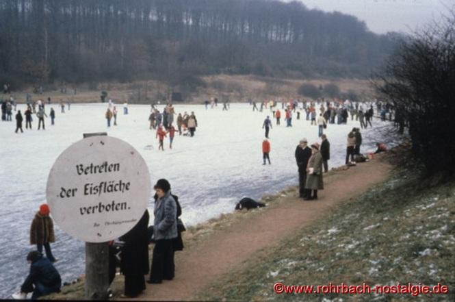 Schlittschuhfahrer und Spaziergänger auf dem zugefrorenen Weiher