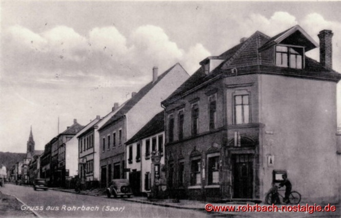 1939 Die Kaiserstraße (rechts das Gasthaus Zum Mühlenhannes) Etwas oberhalb des Gasthauses befand sich einst der Dorfbrunnen mit zwei erhaltenen Trögen; das Brunnenwasser lief über die Straße zu den Wiesen von gegenüber und bew