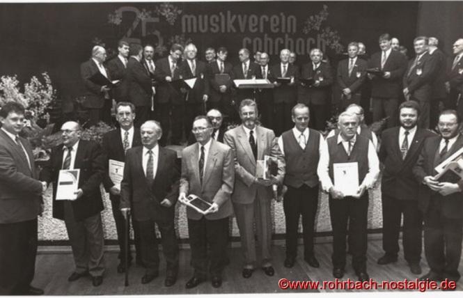 1997 feiert der Musikverein mit einem Festkommers in der TG Turnhalle sein 25-jähriges Bestehen. Vorsitzender Stefan Abel links im Bild ehrt aktive und passive Mitgliede. Im Hintergrund auf der Bühne die Sänger des Männerchores 1860 Rohrbach