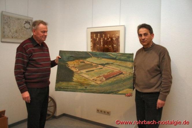 Karl Abel übergibt dem Archivar der Rohrbacher Heimatfreunde Werner Schmitt (links auf dem Foto) ein Gemälde vom Werksgelände der Firma Ernst Heckel zur Ausgestaltung der Heimatstube im Gebäude der Stadtwerke in der Bahnhofsstraße