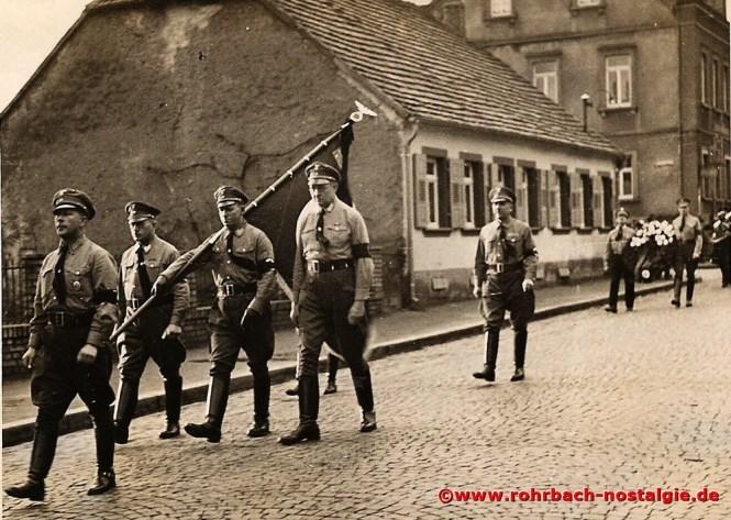 1936 Die politische Führung Rohrbachs bei einer Beerdigung. Vorne Andreas Badar, dahinter rechts neben dem Banner Walter Butenschön. Im Hintergrund das frühere Gasthaus Zum Aules