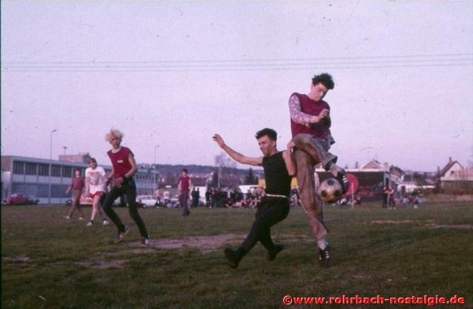 1984 am Ostersamstag. Campino und seine Freunde spielen gegen eine Rohrbacher Fußballmannschaft auf einer Wiese vor dem Umspannwerk. Im Hintergrund die Punkkneipe Tote Hose
