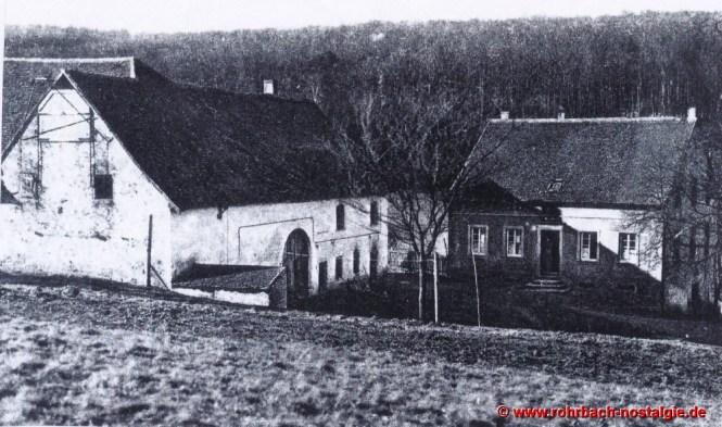 Um 1930 das Anwesen von Ludwig Pauly. Links ist das Wohnhaus mit Stall, Scheune und Heuspeicher. Rechts ist das Wohnhaus mit Gastwirtschaft zu sehen, das 1876 von Christian Riedschy, der in die Familie Hussong einheiratet, erbaut. Hier befindet bis zum Jahr 1982 das Gasthaus von Hannelore und Lothar Kaiser