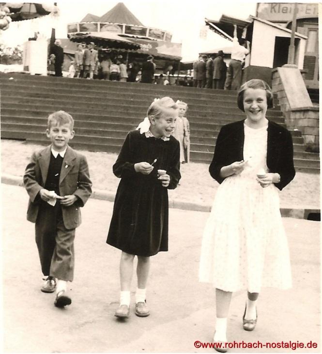 1956 Blick von der Bahnhofstraße auf den Marktplatz mit den Karussells und den Verkaufsständen. Auf dem Foto die Kinder Karl und Anita Abel sowie Margarete Jakob
